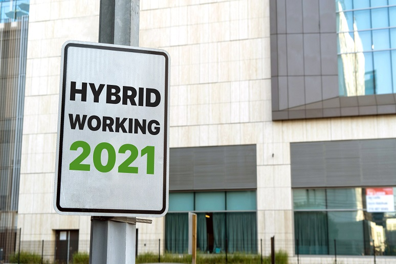 """Photo of sign saying """"hybrid work 2021"""" in front of office building"""