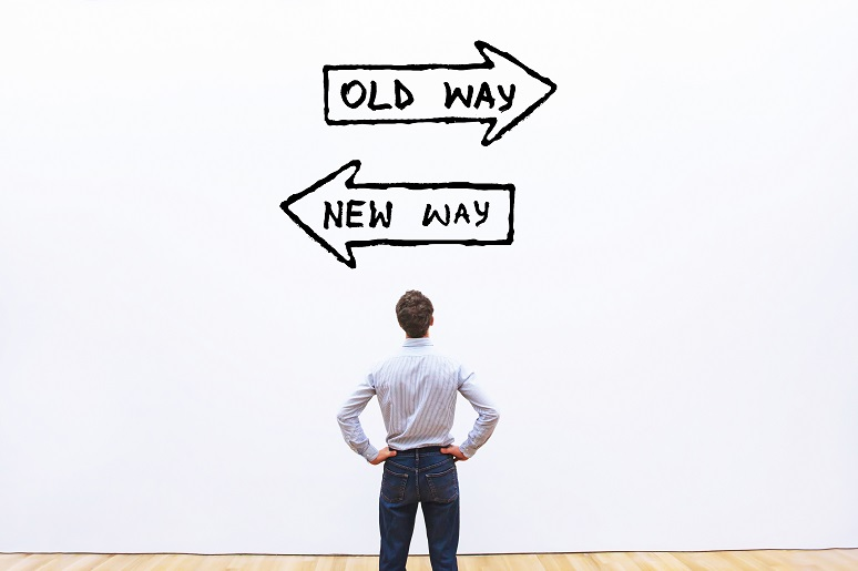 Business man starting at old way/new way arrows