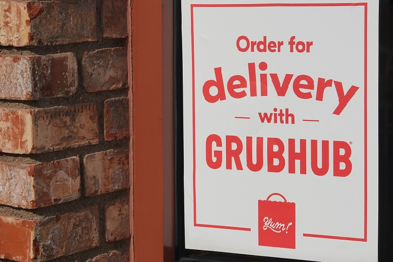 Photo of a restaurant door with a Grubhub sign