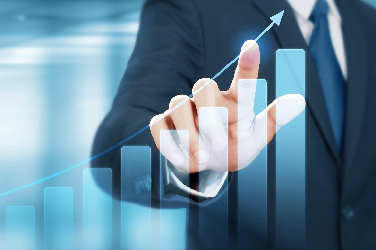 A business person pointing to a chart with growth