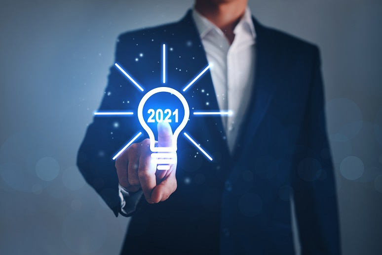 A business person pressing a lightbulb that says 2021