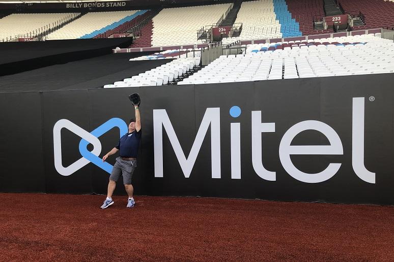 A Mitel logo at a baseball stadium