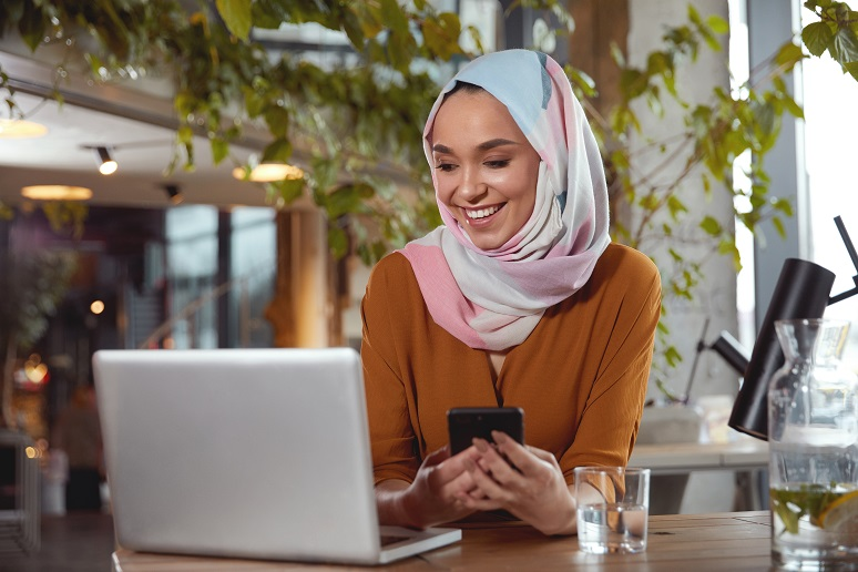 A woman with a hijab reading technology news