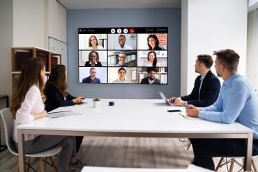 Photo showing virtual meeting with some people in office others remote