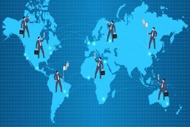 illustration of businessmen planting flags around the globe