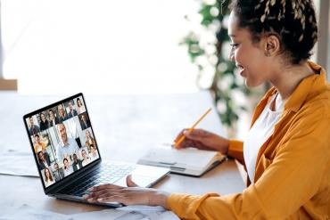 Young business professional collaborating with colleagues via video meeting