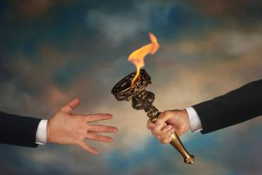 Photo showing hand off of torch from one CEO to the next