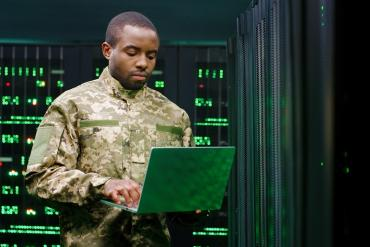 A military officer working on IT equipment