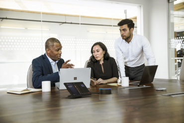 Employees using a Microsoft Teams intelligent speaker in their office.