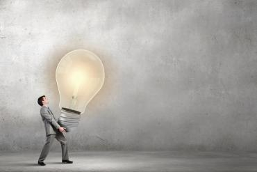 Photo illustration of a man carrying an oversized lightbulb