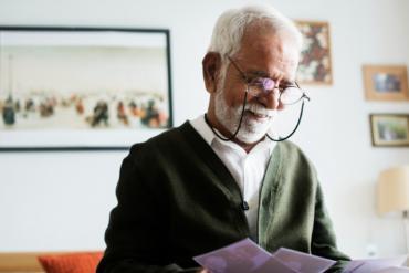 White-haired man reading brochures