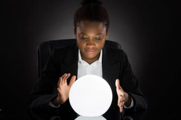 Young businesswoman looking into crystal ball