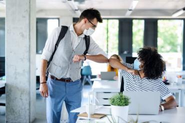 Young professionals elbow-bumping as they return to the office
