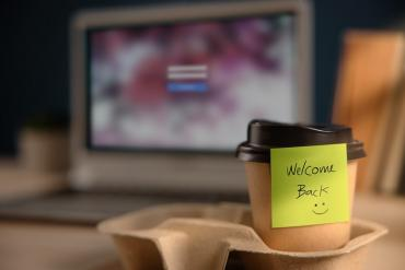 Photo of paper coffee cup with welcome back sticky note