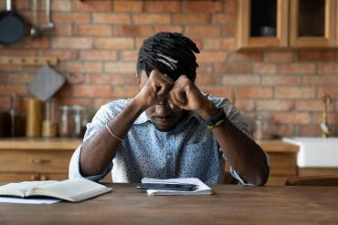 Photo of young man looking overwhelmed as he stares at smartphone