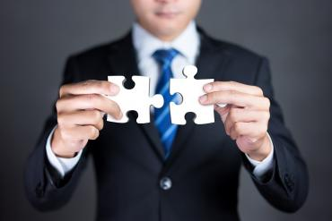 A business person putting two pieces together